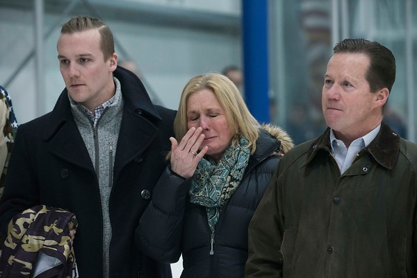 SAM GORESH/Staff photo. Sue Hines wipes away tears as she stands between her husband Steven Hines (right) and son Trevor Hines (left) as they are honored before the hockey game in memory of Sue and Steve Hine's son Derek Hines who was killed while serving with the Airborne Rangers in Afghanistan in 2005. 2/18/17