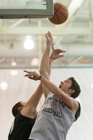 SAM GORESH/Staff photo. Marblehead senior Derek Marino goes up for as basket as junior Dewey Millett attempts to block him during their practice at Marblehead High School. 2/12/17