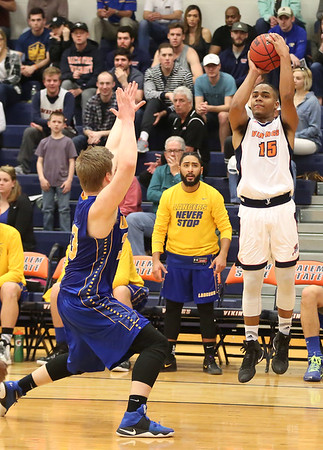 HADLEY GREEN/ Staff photo <br /> Salem State's Alexander Santos (15) shoots while Worcester's Shaun McCarthy (33) plays defense at the Salem State v. Worcester State MASCAC Tournament Championship game held at the Twohig Gymnasium at Salem State on Saturday, February 25, 2017.