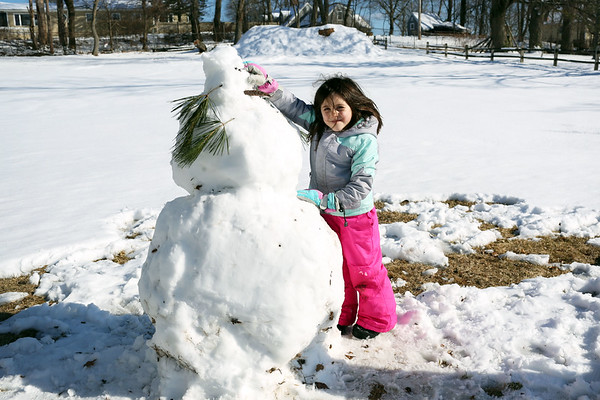 HADLEY GREEN/Staff photo<br /> Nina Saenz, 5, of Beverly, puts the finishing touches on a snowman she made at Lynch Park in Beverly. <br /> <br /> 02/18/18