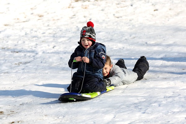 HADLEY GREEN/Staff photo<br /> Landon Chesna, 8, of Danvers, pushes Anthony Capurso, 5, of Beverly, down a hill at Endicott Park. <br /> 02/18/18