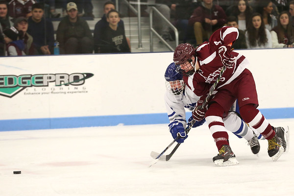 HADLEY GREEN/Staff photo<br /> Danvers' John Kelter (2) and Gloucester's EJ Field (3) vie for the puck at the Danvers v. Gloucester boys hockey game at Endicott College.<br /> <br /> 02/09/18