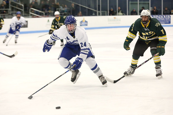 HADLEY GREEN/Staff photo<br /> Danvers' Colin Desmond (24) skates to the puck at the Danvers v. North Reading boys hockey game at Endicott College. <br /> <br /> 02/23/18
