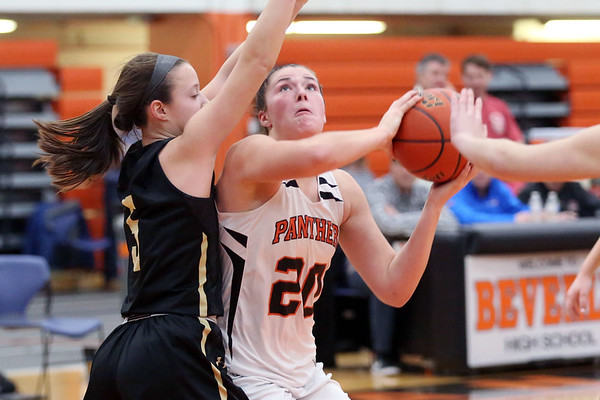 HADLEY GREEN/Staff photo<br /> Beverly's Alyssa Moreland (20) looks to the basket while Bishop Fenwick's Sammi Gallant (5) plays defense at the Beverly v. Bishop Fenwick girls basketball game at Beverly High School.<br /> <br /> 02/18/18