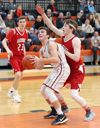 HADLEY GREEN/Staff photo<br /> Gloucester's Benjamin Oliver (2) shoots while Masconomet's Colby Jacques (2) plays defense at the Gloucester v. Masconomet boys basketball game at Beverly High School.<br /> <br /> 02/18/18