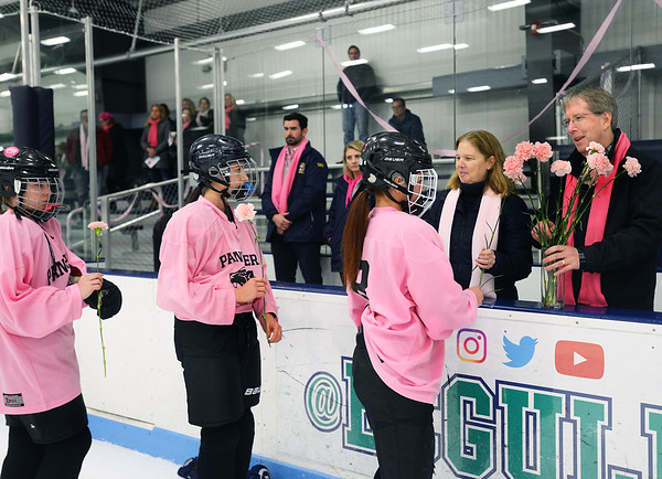 CARL RUSSO/Staff photo. Colleen Ritzer's parents, Peggie and Tom accept pink carnations from Beverly/Danvers sophomore hockey player, Lily Cook, right  and other players. Both teams presented the flowers to the Ritzers before the start of the game. <br /> <br /> The annual Colleen Ritzer memorial hockey game between Andover high and Beverly/Danvers was played on January 9, Wednesday night at the Raymond Bourque arena at Endicott College. The game benefits the Colleen Ritzer Memorial Scholarship Fund. <br /> <br /> Colleen Ritzer of Andover, a Danvers high school teacher was murdered in 2013 by her student. 1/9/2019