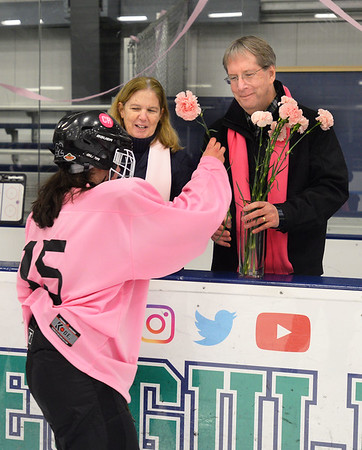 CARL RUSSO/Staff photo. Colleen Ritzer's parents, Peggie and Tom accept pink carnations from Beverly/Danvers freshman hockey player, Sofiya Palermo. Both teams presented the flowers to the Ritzers before the start of the game. <br /> <br /> The annual Colleen Ritzer memorial hockey game between Andover high and Beverly/Danvers was played on January 9, Wednesday night at the Raymond Bourque arena at Endicott College. The game benefits the Colleen Ritzer Memorial Scholarship Fund. <br /> <br /> Colleen Ritzer of Andover, a Danvers high school teacher was murdered in 2013 by her student. 1/9/2019