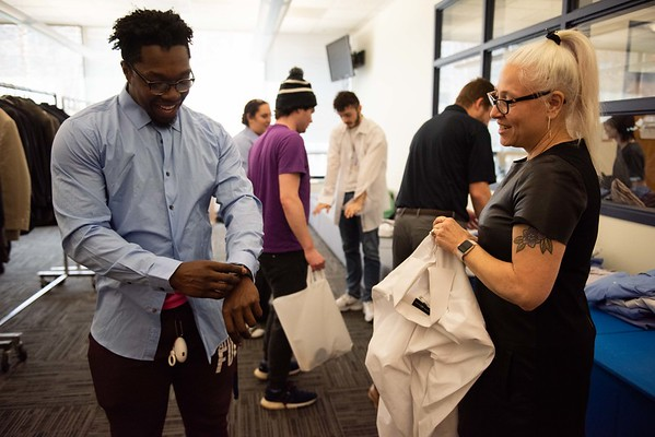 AJ Nwokeji, 24 years old, a senior of Salem State, left, is helped by Peabody J. Crew's Annika Wagner, right, with sizing a shirt. Salem State held it's Career Closet day at Ellison Campus Center on Thursday. RYAN MCBRIDE/Staff photo 2/20/20