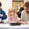 Henry Hildreth-Derocher, 6, left, Willa Hildreth-Derocher, 3, center, and Steven Derocher, right, make their Mardi Gras masks. Hamilton Wenham Library hosted a Mardi Gras mask making day on Saturday. RYAN MCBRIDE/Staff photo 2/22/20
