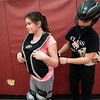 Aleena Brown, 11 years old, of Gloucester, is helped by Gaby Olsen, 16 years old, of Gloucester, during softball camp. The GHS youth softball clinic took place at Gloucester High School Thursday morning. RYAN MCBRIDE/Staff photo 2/20/20