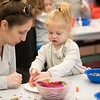 Alexandra Capachietti, left and Emma Zurbrigg, 2, right, make a Mardi Gras mask. Hamilton Wenham Library hosted a Mardi Gras mask making day on Saturday. RYAN MCBRIDE/Staff photo 2/22/20