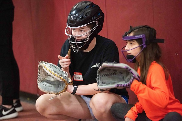 Chloe De Gaspe Beaubien, 15 years old, left, helps Adrianna Orlando, 10 years old, of Gloucester, right, giving her tips for the catcher position. The GHS youth softball clinic took place at Gloucester High School Thursday morning. RYAN MCBRIDE/Staff photo 2/20/20