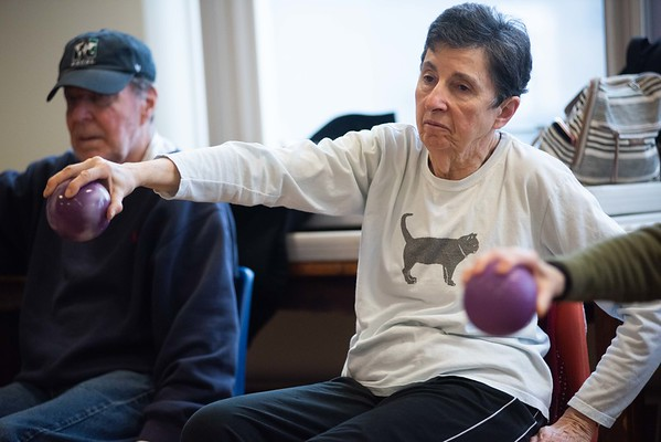 Camile Motta, of Marblehead, stretches her arm with while holding a weight ball. Strength in Motion, the Parkinson's Fitness class runs every Tuesday from 11:00 AM to Noon at the Marblehead Council on Aging. RYAN MCBRIDE/Staff photo 2/25/20