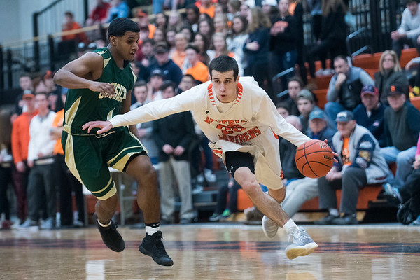 Beverly junior Luigi Derrane races down the court with the ball as Lynn Classical senior Gilbert Minaya chases him on defense in their game at Beverly High School. Lynn Classical won the game 68-65. 1/27/17