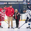 SAM GORESH/Staff photo. Masconomet head coach Andrew Jackson helps Sally Driscoll as she does the ceremonial puck drop before the inaugural 'Can Do' Classic between Masconomet Peabody. The game was played in honor of Sally Driscoll's husband, Bob Driscoll, who passed away in 2016  and was a Masconomet hockey coach and long-time Peabody resident and city councilor. 1/2/17