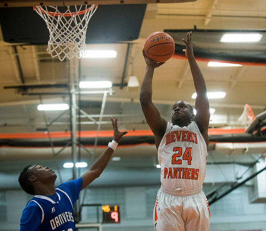 Beverly senior Hugh Calice goes up for a basket as Danvers junior Tahg Cokley attempts to stop him on defense in their game at Beverly High School. 1/3/17