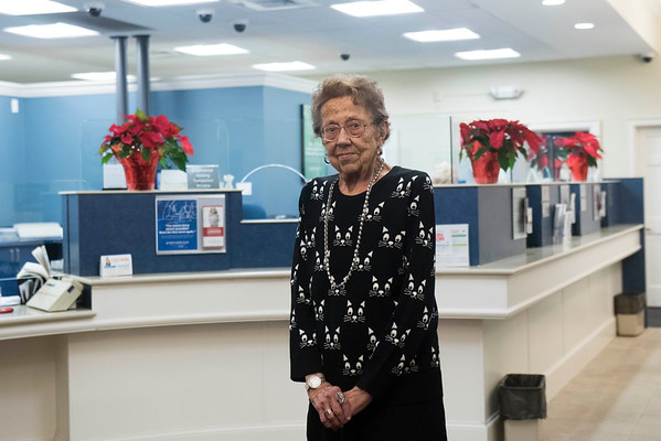 SAM GORESH/Staff photo. Bertha Mulley poses for a portrait at North Shore Bank in Peabody were she has worked for 65 years, she will be retiring next week. 1/3/17
