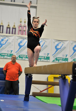NICOLAS TANNER/Photo.     A Gloucester high school gymnastics team member competes on the beam against Beverly high school while a coach for Beverly looks on, at a meet held at the Sterling Center YMCA in Beverly. 1/19/17