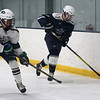 HADLEY GREEN/Staff photo<br /> Hamilton-Wenham's Luke McClintock (13) moves the puck while Essex Tech's Nick Ippolito (9) plays defense at the Essex Tech v. Hamilton-Wenham boys hockey game at the Essex Sports Center. <br /> <br /> 01/31/18