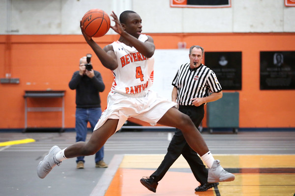 HADLEY GREEN/Staff photo<br /> Beverly's Marje Mulumba (4) saves the ball from going out of bounds at the Beverly v. Lynn Classical boys basketball game at Beverly High School.<br /> <br /> 1/09/17