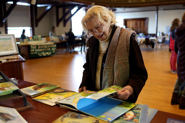 HADLEY GREEN/Staff photo<br /> Anna Comolli of Gloucester peruses books at the Cape Ann Reads community fair at Gloucester City Hall.<br /> <br /> 01/27/18