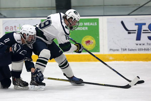 HADLEY GREEN/Staff photo<br /> Essex Tech's Chris Masta (19) and Hamilton-Wenham's Clint Goudreau (11) vie for the puck at the Essex Tech v. Hamilton-Wenham boys hockey game at the Essex Sports Center. <br /> <br /> 01/31/18