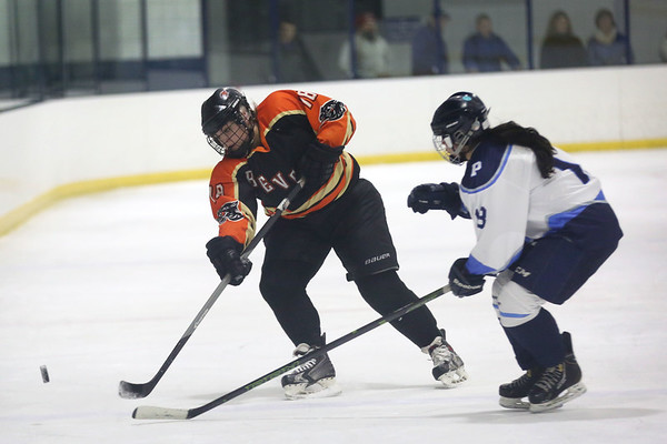 HADLEY GREEN/Staff photo<br /> Beverly's Megan Caley (18) moves the puck while Peabody's Cassie Mirasolo (13) plays defense at the Peabody v. Beverly girls hockey game at the McVann-O'Keefe Rink in Peabody. <br /> <br /> 01/17/18