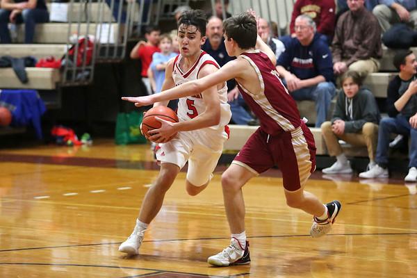 HADLEY GREEN/Staff photo<br /> Masconomet's Matt Dzwil (5) dribbles while Newburyport's Jacob Robertson (13) plays defense at the Masconomet v. Newburyport boys basketball game.<br /> <br /> 1/12/17