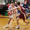 HADLEY GREEN/Staff photo<br /> Masconomet's Matt Dzwil (5) dribbles while Newburyport's Jacob Robertson (13) plays defense at the Masconomet v. Newburyport boys basketball game.<br /> <br /> 1/12/17