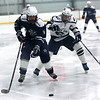 HADLEY GREEN/Staff photo<br /> Hamilton-Wenham's Aidan Doly (14) moves the puck while Essex Tech's Chris Masta (19) chases him at the Essex Tech v. Hamilton-Wenham boys hockey game at the Essex Sports Center. <br /> <br /> 01/31/18