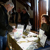 HADLEY GREEN/Staff photo<br /> Thom Adorney of Beverly speaks to Ashley Pengelly of Beverly while looking at books at the Cape Ann Reads community fair at Gloucester City Hall.<br /> <br /> 01/27/18