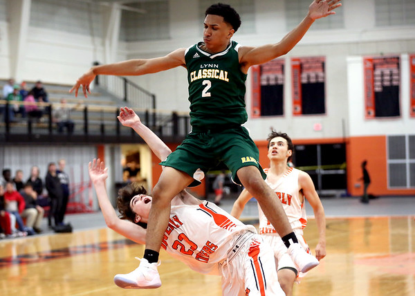 HADLEY GREEN/Staff photo<br /> Lynn Classical's Deontae Plouffe (2) jumps over Beverly's Matt Rawding (23) at the Beverly v. Lynn Classical boys basketball game at Beverly High School.<br /> <br /> 1/09/17