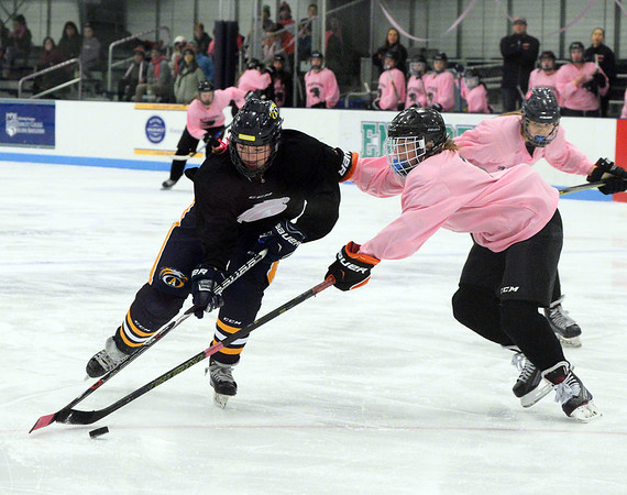 CARL RUSSO/Staff photo. Andover's Lilly Reeves, left, moves the puck against Beverly/Danvers junior, Tori Shea in hockey action. <br /> <br /> The annual Colleen Ritzer memorial hockey game between Andover high and Beverly/Danvers was played Wednesday night on January 9 at the Raymond Bourque arena at Endicott College. <br /> <br /> The game benefits the Colleen Ritzer Memorial Scholarship Fund. Colleen Ritzer of Andover, a Danvers high school teacher was murdered in 2013 by her student. 1/9/2019