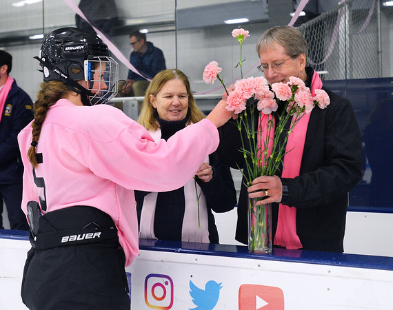 CARL RUSSO/Staff photo. Colleen Ritzer's parents, Peggie and Tom accept pink carnations from Beverly/Danvers junior hockey player, Emma Thibodeau. Both teams presented the flowers to the Ritzers before the start of the game. <br /> <br /> The annual Colleen Ritzer memorial hockey game between Andover high and Beverly/Danvers was played on January 9, Wednesday night at the Raymond Bourque arena at Endicott College. The game benefits the Colleen Ritzer Memorial Scholarship Fund. <br /> <br /> Colleen Ritzer of Andover, a Danvers high school teacher was murdered in 2013 by her student. 1/9/2019
