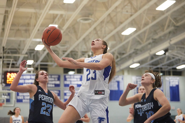 Danver's Autumn James tries a reverse layup over Peabody's Georgia Leon (23) at Danvers High School, December 17, 2018. Jared Charney / Photo