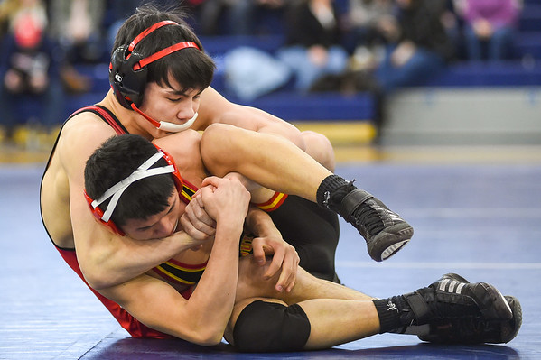 JAIME CAMPOS/Staff photo<br /> <br /> Liam McAveney of Masconomet wraps up Josiah Quincy's Ricky Sun in the in the 126lbs weight class during a wrestling meet at St. John's Prep in Danvers<br /> <br /> 1/21/2019