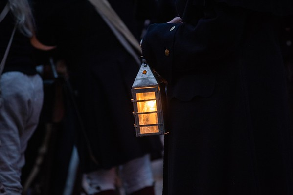 A lantern glows during blue hour as Glover's Marblehead Regiment joined at the Old Town House. They marched to Burial Hill in honor of the contributions and sacrifices of Marblehead residents during the Revolutionary War. RYAN MCBRIDE/Staff photo 2/1/20