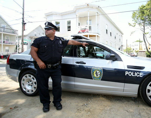 Salem Patrolman Victor Ruiz stands on Leavitt Street in the Point Neighborhood on Tuesday afternoon. The Salem Police Department has been beefing up its presence in the neighborhood, especially at nighttime when outdoor parties and gatherings could occur. DAVID LE/Staff photo. 7/29/14.