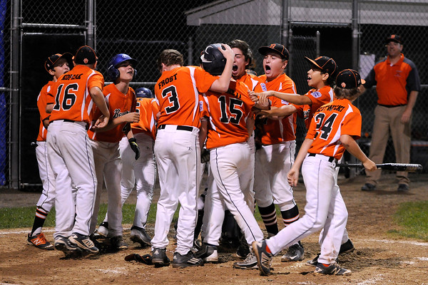 TIM JEAN/Staff photo Beverly's Joey Loreti is swarmed by his teammates after hitting a home run againt Andover during the Section 4 Little League all-star championship game.  7/23/16