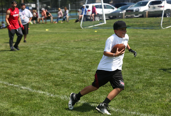 HADLEY GREEN/Staff photo<br /> Raymond Beaulieu of Danvers runs with the ball after catching a pass from Patriots wide receiver Julian Edelman at the Julian Edelman Football Clinic at Danvers High School. 7/15/17