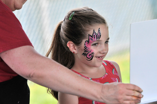 TIM JEAN/Staff photo<br /> Raylee Anthony, 7, of Danvers looks in a mirror of her face painted by Katy Meighan during the 3rd Annual Field Day and Scoop-Ah-Bowl party and Family Festival at Plains Park in Danvers. 7/1/17