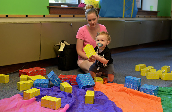RYAN HUTTON/ Staff photo<br />  Sam Martel, 1, and his mom Alison build with blocks at the Salem Public Library's kid's summer reading program kick off party on Wednesday.