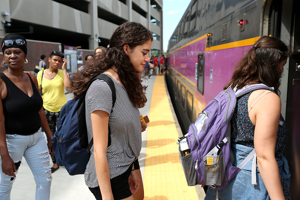 HADLEY GREEN/Staff photo<br /> Elena Messina, who reverse commutes from Boston to the North Shore for her internship, boards a commuter rail train at the end of the day. 7/17/17