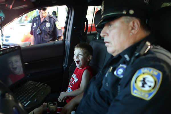 HADLEY GREEN/Staff photo<br /> Jared Carpenter, 5, of Salem, is amazed after beeping the horn in policeman William Jennings' patrol car at the Salem National Night Out on the Salem Common. 8/01/17