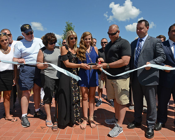 RYAN HUTTON/ Staff photo<br /> The family of Ella Jade O'Donnell, a local 10-year-old who died of brain cancer last year, cut the ribbon on the playground named in her honor at the South Memorial School in Peabody on Wednesday.  At center is her older sister Sydney Lynn, her mother Erin, left, and her father Dennis, right.