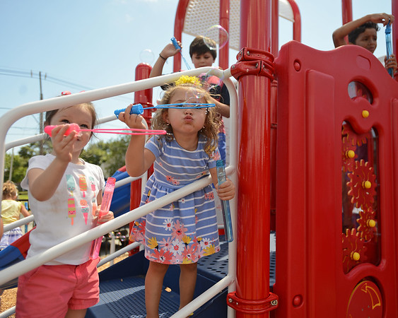 RYAN HUTTON/ Staff photo<br /> Lily Kellher, 4, left, and Grace Vaz, 3, right, blow bubbles on the new jungle gym during the opening of a new playground at South Memorial School in Peabody on Wednesday. The playground is named in honor of Ella Jade O'Donnell, a local 10-year-old who died of brain cancer last year.