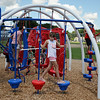 RYAN HUTTON/ Staff photo<br /> Madeline Mahoney, 11, climbs across the jungle gym during the opening of a new playground at South Memorial School in Peabody on Wednesday. The playground is named in honor of Ella Jade O'Donnell, a local 10-year-old who died of brain cancer last year.