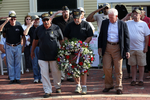 HADLEY GREEN/Staff photo<br /> Veterans salute while commemorating a wreath for soldiers who died in combat during at the ribbon cutting ceremony for the new Vietnam Veterans Memorial Plaza at One Ellis Square in downtown Beverly. 7/28/17