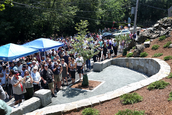 HADLEY GREEN/Staff photo<br /> People stand facing the new Proctor's Ledge memorial while Rev. Jeffrey Barz-Snell leads a prayer dedicating the site. Proctor's Ledge is believed to be the location where 19 innocent people were hanged in 1692 for the supposed crime of witchcraft. 7/18/17