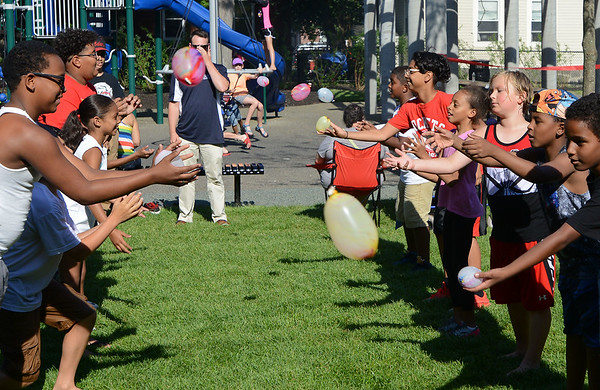RYAN HUTTON/ Staff photo<br /> About a dozen children compete in a water balloon toss during the grand re-opening of the Mary Jane Lee Park in the Point in Salem on Wednesday.